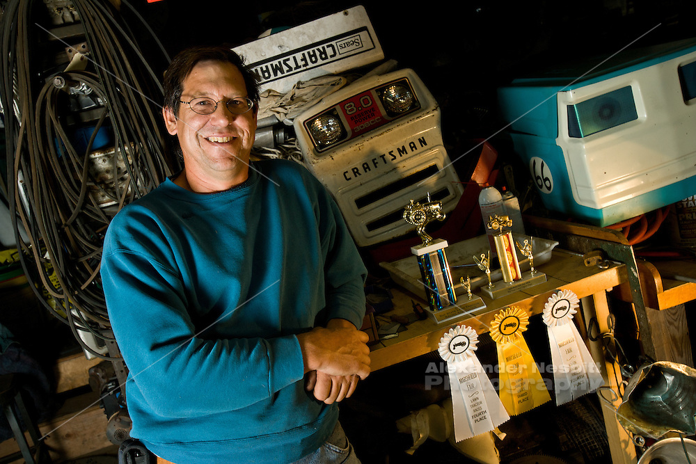 Portsmouth, RI - 2010 - Lawn tractor racing enthusiast Mathew Kent with his trophies and Tractor parts in his workshop.