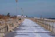 The boardwalk is covered by snow on a cold day in January.
