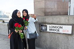 June 11, 2017 - London, London, UK - LONDON, UK.  Two women take a selfie with red roses on London Bridge this afternoon. 1,000 red roses with messages of ''love and solidarity'' were given to passers by on London Bridge today. (Credit Image: © Vickie Flores/London News Pictures via ZUMA Wire)