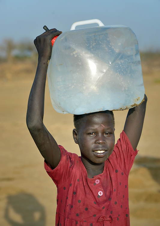 A girl carries water from a well in the internally displaced persons camp in Turalei, South Sudan. Families started arriving here shortly after fighting broke out in December 2013, and new families continued to arrive in March 2014 as fighting continued. Many are living in the open and under trees. The ACT Alliance is providing the displaced families and the host communities affected by their presence with a variety of support, including new wells.