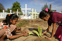 Right to left, sisters Shrianna and Brianna Barthelot, 11 and 13, light candles for their older brother and parents who who died in the tsunami, using leaves to block the wind, Batticaloa, Sri Lanka, July 10, 2005. They are now living with relatives at night and spending most of their days at the convent where the rest of their village is staying.