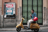 November 1989, Rome, Italy --- Teenager on a Moped Eating an Ice Cream Cone --- Image by © Owen Franken