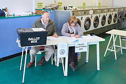© Licensed to London News Pictures.  07/05/2015. OXFORD, UK. General view (GV) of a polling station inside a launderette in Headington, near Oxford. *** Taken from outside polling station with permission of officials and voters ***.  Photo credit: Cliff Hide/LNP