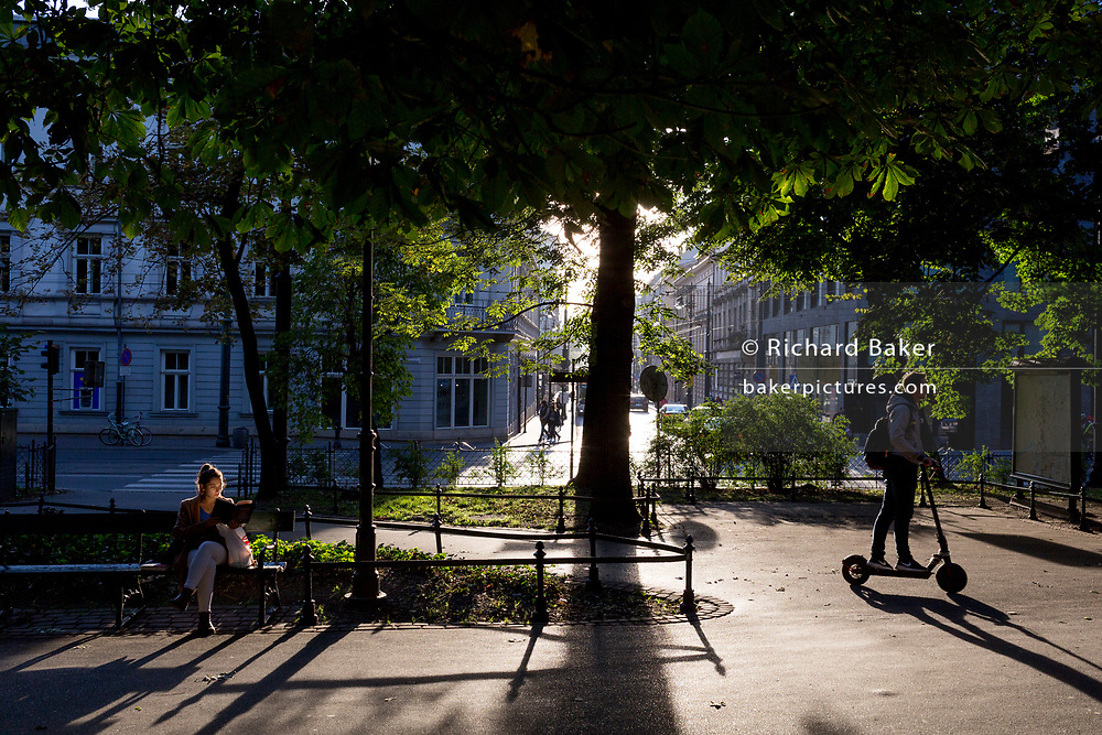 Seated on a park bench, as a scooter passes-by, a young Polish woman reads a book in late afternoon sunshine, on 23rd September 2019, in Krakow, Malopolska, Poland.
