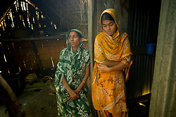 """Mamtaz Begum, 35,  sits with her daughter Neherum, 17, and family in her house in the fishing village of South Tetulbarian in Barguna Sadar upazila  in Bangladesh  October 20, 2010 . Her husband died in a boat accident after capsizing because violent weather. Her mother died later in a cyclone and now she is left with 4 children to feed and very little means to support them. Because of climate change, the seas are getting more violent, less predictable and boats are capsizing more frequently. Twenty percent of the women in this village are widows because so many have lost their husbands in the seas. Coastal and fishing populations are particularly vulnerable and Fishing communities in Bangladesh are subject not only to sea-level rise, but also flooding and increased typhoons. Erosion as a result of stronger and higher tides, cyclones and storm surges is eating away Bangladesh's southern coast.  Yet the largely fishing community cannot live without the sea. """"We only know how to catch fish,"""" say the fishermen. ( Ami Vitale)"""