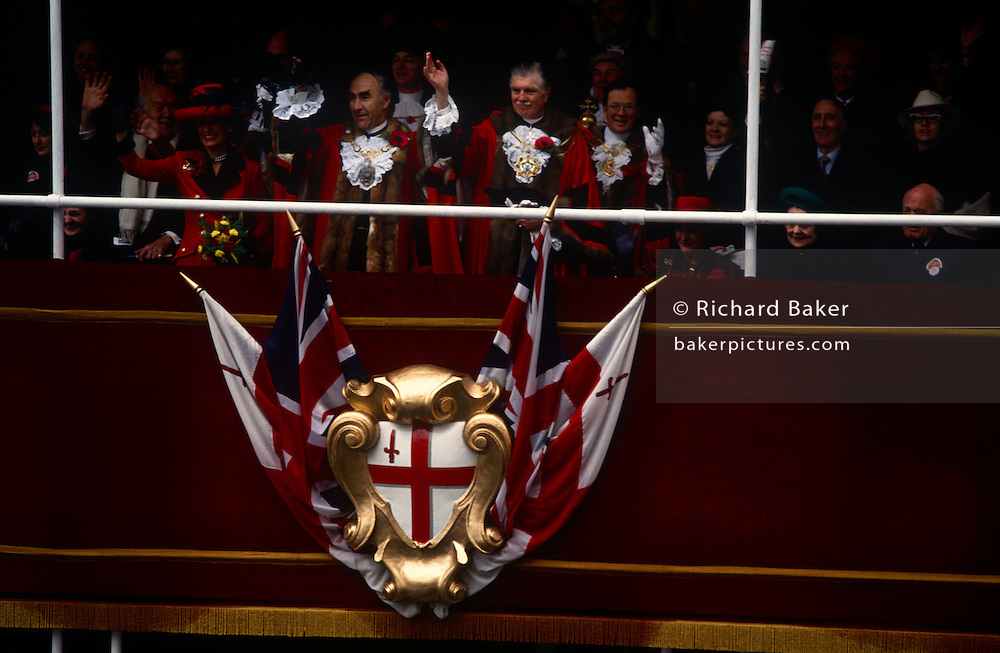 The Lord Mayor of London waves to crowds and passing carnival floats in this Lord Mayor's Show - the oldest, longest, most popular civic procession in the world. Surrounded by City fathers and dignitaries up on a rostrum outside his official residence, the VIP wears the gowns of office during this annual event to honour the new Lord Mayor in the financial district of London. The show has floated, rolled, trotted, marched and occasionally fought its way through almost 800 years of London history, survived the black death and the blitz and arrived in the 21st century as one of the world's best-loved pageants. ...