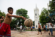 Puerto Princesa, Palawan, Philippines - July 2, 2019: People play basketball on a court in Rizal Park across from Immaculate Conception Cathedral in Puerto Princesa.