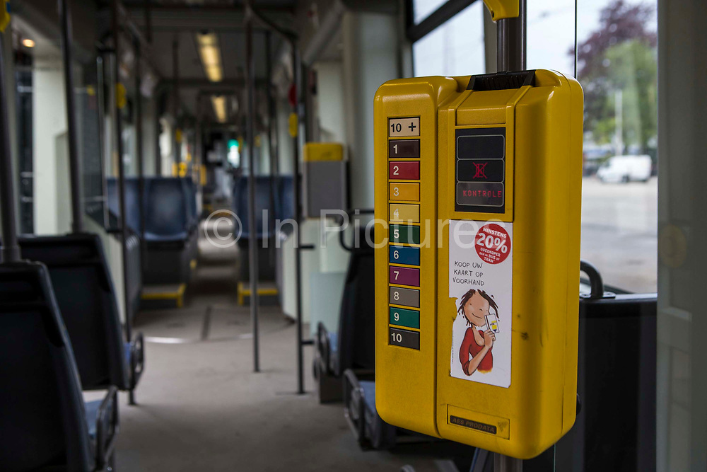 A yellow self-service ticket machine box on board a De Lijn electric tram bus in Ghent, Belgium.