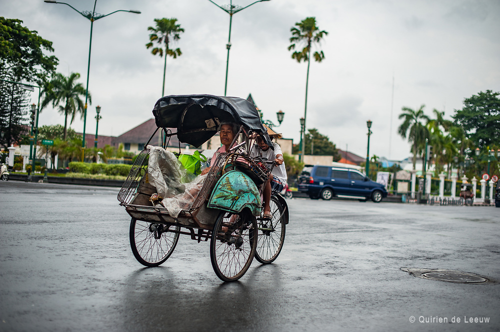 A young boy drives an elder woman in a becak on the Medan Merdeka (freedom square) and the former Koningsplein square during the period of Dutch rule.