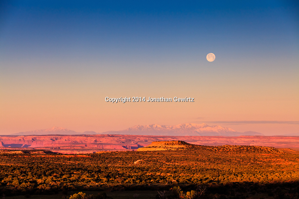 The full moon sets at sunrise over Utah's Canyonlands National Park and the Green River plateau, with Mount Pennell and Capitol Reef National Park in the distant background. WATERMARKS WILL NOT APPEAR ON PRINTS OR LICENSED IMAGES.<br /> <br /> Licensing: https://tandemstock.com/assets/31596080
