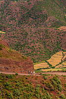 People walking up the steep dirt road leading to Lalibela, Ethiopia.