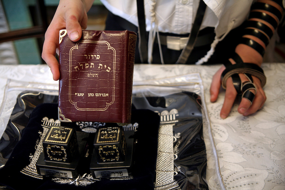 The items needed for an Orthodox Jewish man during Morning Prayer. A copy of siddur (prayer book containing daily prayers) the Tallit and two tefillins, the leather straps from the arm Tefillin is being worn. Once all these items have been put on correctly Morning Prayer can begin.