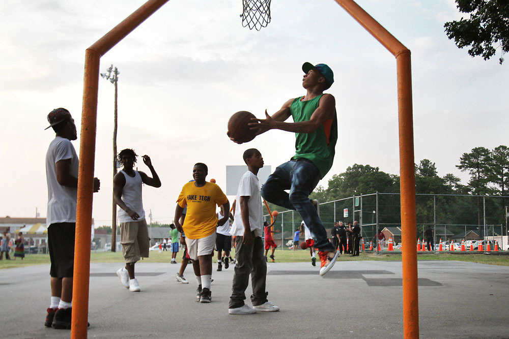 Corvin Kelly, 22, right, leaps into the air as he shots a basket while playing basketball during the first Summer Night Lights event on Friday at Meadowbrook Park.