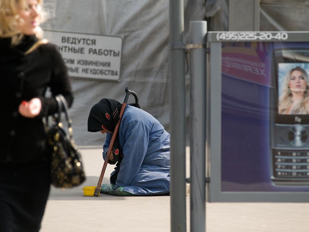 Aeltere Frau bettelt vor einer Werbung fuer Mobiltelefone auf einer Strasse im Zentrum der russischen Hauptstadt Moskau. <br /> <br /> Old woman is begging infront of an advertising for mobil phones on a street in the center of the Russian capitol Moscow .