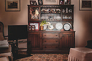 Dark wood sideboard with decorative elements and photographs in a lounge with floral carpet.