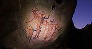 Large red-and-black human figures wearing elaborate headdresses dominate the mural at Cueva de La Flechas (Cave of the Arrows) in the Sierra de San Francisco, Baja California Sur, Mexico. The cave painting site gets its name from two human figures pierced with arrows. The region, rich in pictograph and petroglyph sites, was named a UNESCO World Heritage Site in 1993.