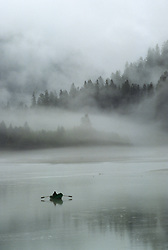 United States, Washington State, near Diablo. Fisherman rowing in mist on Ross Lake in Ross Lake National Recreation Area