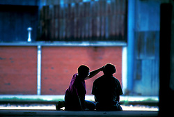 Stock photo of the silhouette of two boys sitting outside