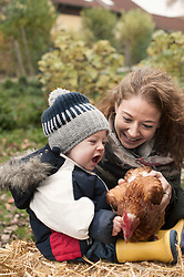 Mother and son playing with chicken bird in the poultry farm, Bavaria, Germany