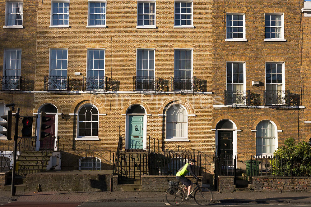 Fine examples of early 19th century Georgian Regency terraced housing on the Camberwell New Road, south London. A cyclist passes-by on his way north towards the Oval. Clean brickwork and window pedament arches show the pre-Victorian era building style. Camberwell New Road is part of the A202. It goes from Camberwell to Kennington Oval. It was a turnpike road authorized by Act of Parliament in 1818, just after the construction in 1816 of the first Vauxhall Bridge, which it leads to, thus providing a second route from Camberwell to central London. Camberwell New Road is the longest Georgian Road in England.