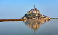 """Scenic view of the tidal island  of Mont Saint Michel at high tide surrounded and its medieval abbey of Saint Michel. Normandy France.<br /> <br /> The tides vary greatly, at roughly 14 metres (46 ft) between highest and lowest water marks. Popularly nicknamed """"St. Michael in peril of the sea"""" by medieval pilgrims making their way across the flats, the mount can still pose dangers for visitors who avoid the causeway and attempt the hazardous walk across the sands from the neighbouring coast."""