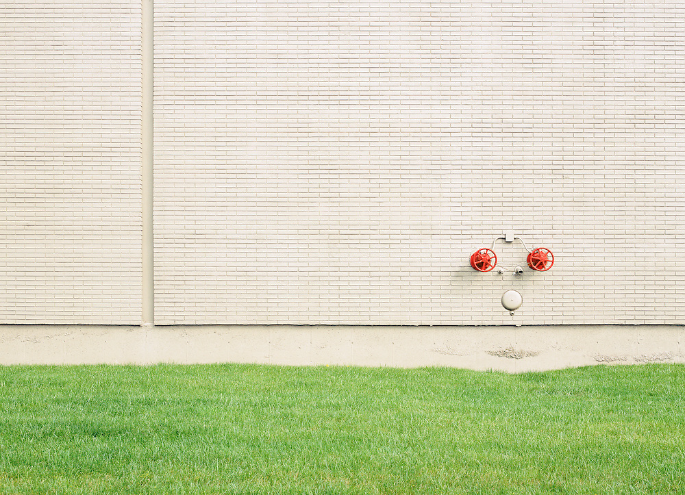 Plain brick wall with red wheels controlling water in case of a fire.