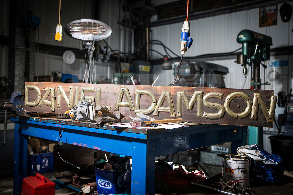 """© Licensed to London News Pictures. 04/05/2016. Birkenhead UK. Picture shows the Daniel Adamson's name plate during restoration work at the Canada Dock volunteer workshop. The Daniel Adamson steam boat has been bought back to operational service after a £5M restoration. The coal fired steam tug is the last surviving steam powered tug built on the Mersey and is believed to be the oldest operational Mersey built ship in the world. The """"Danny"""" (originally named the Ralph Brocklebank) was built at Camel Laird ship yard in Birkenhead & launched in 1903. She worked the canal's & carried passengers across the Mersey & during WW1 had a stint working for the Royal Navy in Liverpool. The """"Danny"""" was refitted in the 30's in an art deco style. Withdrawn from service in 1984 by 2014 she was due for scrapping until Mersey tug skipper Dan Cross bought her for £1 and the campaign to save her was underway. Photo credit: Andrew McCaren/LNP ** More information available here http://tinyurl.com/jsucxaq **"""