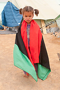 Tunisia 2011. Remada camp for refugees from Libya. Young girl , Henadi, wrapped in the Libyan flag after the demonstration.