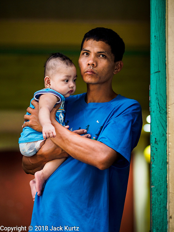 28 JANUARY 2018 - LEGAZPI, ALBAY, PHILIPPINES:  A man and his infant son watch a Catholic mass for evacuees at the evacuation shelter for people from Barangay (community) Matanag in Albay Central School in Legazpi. People from the community have been in the shelter since Mayon volcano started erupting two weeks ago. There are about 500 families at the shelter, around 2,000 people. More than 80,000 people have been evacuated from communities around the volcano and are living in shelters and camps outside of the evacuation zone. The Philippine government is preparing to house the people for up to three months.     PHOTO BY JACK KURTZ