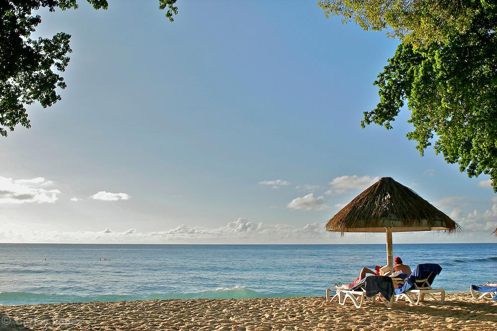 A couple of tourist having a rest in one caribbean beach of Barbados..Una pareja de turstas descansa en un playa de la isla de barbados en el Caribe.
