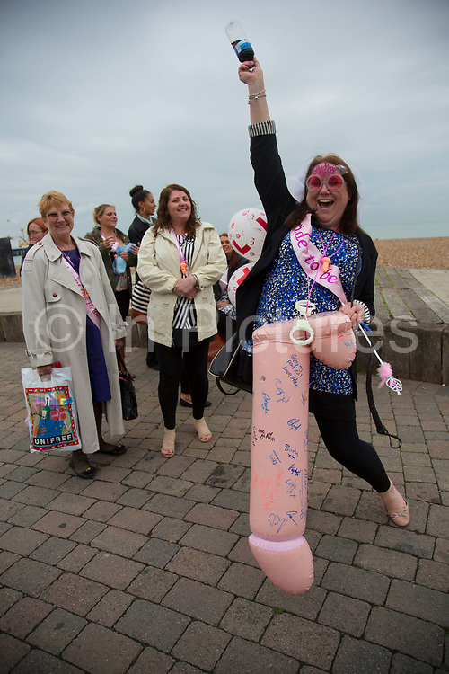Woman and her girlfriends and family out on her hen party on the sea front in Brighton. Wearing a Bride to be sash and plastic handcuffs sha has a giant inflatable penis which has been signed by lots of people. The Hen do for many people is a good excuse to go out with your friends, and get very drunk and often in a lewd way. Brighton, UK.