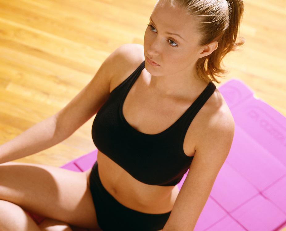 Woman doing yoga in black exercise attire seated on pink mat and wood floor