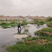 In Bhalswa, north Delhi, below one of the giant open air garbage dump, Ajay cleans the open sewer of grass and branches to avoid garbage blockage  when the monsoon arrives. He makes 300 RP a day (4.5 USD).