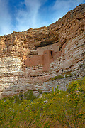 The five-story cliff dwelling known as Montezuma Castle is visible up a sheer limestone cliff in Montezuma Castle National Monument near Camp Verde, Arizona. Montezuma Castle and other cliff dwellings in the area were built and used by the Sinagua people between approximately 1100 and 1425 AD. Montezuma Castle, which contains 45-60 rooms, is one of the best-preserved cliff dwellings in North America, likely due to its placement 90 feet (27 meters) up the cliff and the protection from the elements provided by the rock overhang.