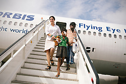 A staff member escorts a young patient down the stairs of the ORBIS Flying Eye Hospital in Kolkata, India. The aircraft offers the latest medical knowledge and training to communities around the world, in order to treat patients and restore sight.