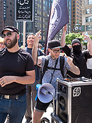 An anti-Trump protester gives double fingers to anti-Sharia law protesters while he plays music through a speaker and holds a bullhorn