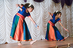 Two young  girls performing a dance on stage celebrating Diwali; Festival of Light,