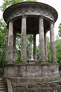 The circular neo-Roman St. Bernards Mineral Well on the Water of Leith near Dean Village, on 26th June 2019, in Edinburgh, Scotland. The St Bernards Well as we have it today was constructed in 1789 to a design by celebrated Edinburgh landscape painter Alexander Nasymth drawing inspiration from the Temple of Vesta at Tivoli in Italy. At the centre of an open pillared dome stands a marble statue of Hygieia, Goddess of Health.