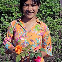 Asia, Nepal, Kathmandu. A Nepali girl holding flowers.