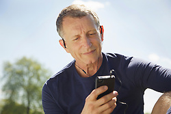 Close up of Mature Man in Park Listening to Music on Smartphone