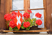 02 AUGUST 2007 -- MURREN, BERN, SWITZERLAND: Flowers and a Swiss flag in a planter box in a window in a home in the Alpine village of Murren, canton of Bern, Switzerland. Murren is about 5,413 feet above sea level and overlooks three of the most popular peaks in the Swiss Alps, the Eiger, the Monk and Jungfrau. In the winter it is a popular ski destination and in the summer mountain climbers and hikers visit the area.   Photo by Jack Kurtz