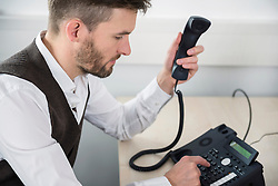 Manager in office dialing landline telephone