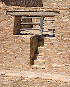 T-shaped passage into ancient stone kiva. Casa Rinconada, occupied about AD 1140-1200, is an isolated great kiva (out of four in Chaco Canyon), built 63 feet (19 m) in diameter with a circular inner bench, masonry firebox, masonry vaults, 34 niches, four large pits for seating roof supports, plus an unusual 39-foot (12 m) passage dug underground through sandstone and shale. Chaco Culture National Historical Park hosts the densest and most exceptional concentration of pueblos in the American Southwest and is a UNESCO World Heritage Site. Chaco Canyon is in remote northwestern New Mexico, between Albuquerque and Farmington, USA. From 850 AD to 1250 AD, Chaco Canyon advanced then declined as a major center of culture for the Ancient Pueblo Peoples. Chacoans quarried sandstone blocks and hauled timber from great distances, assembling fifteen major complexes that remained the largest buildings in North America until the 1800s. Climate change may have led to its abandonment, beginning with a 50-year drought starting in 1130.
