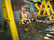11 APRIL 2016 - BANGKOK, THAILAND:  Children in the playground in Mahakan Fort. The community is known for fireworks, fighting cocks and bird cages. Mahakan Fort was built in 1783 during the reign of Siamese King Rama I. It was one of 14 fortresses designed to protect Bangkok from foreign invaders, and only of two remaining, the others have been torn down. A community developed in the fort when people started building houses and moving into it during the reign of King Rama V (1868-1910). The land was expropriated by Bangkok city government in 1992, but the people living in the fort refused to move. In 2004 courts ruled against the residents and said the city could take the land. The final eviction notices were posted in late March 2016. Residents were given until April 30 to move out. After that their homes, some of which are nearly 200 years old, will be destroyed.       PHOTO BY JACK KURTZ