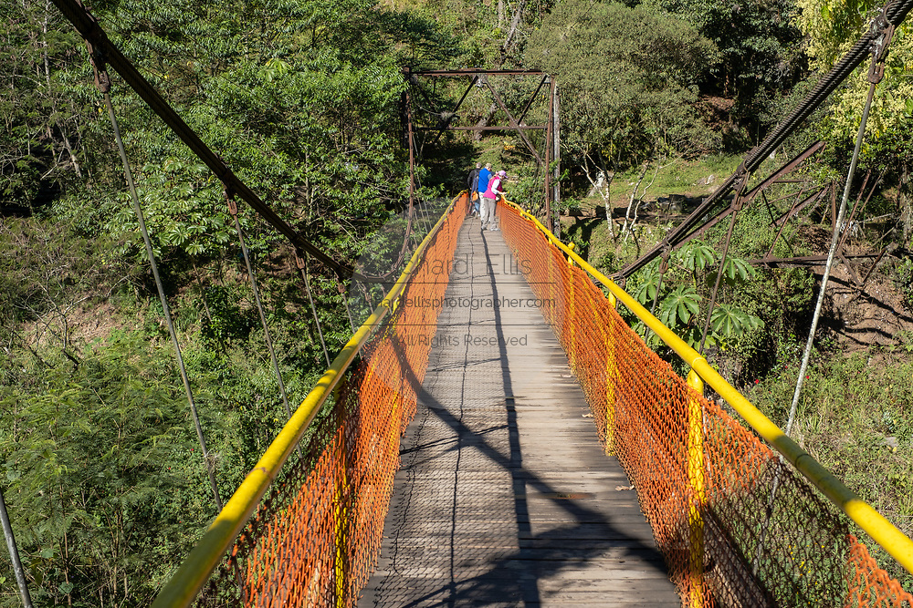 Tourists cross a wooden suspension bridge on the way to the Cascada de Texolo waterfall near Xico, Veracruz, Mexico. The 80-foot high waterfall was used in the movie Romancing the Stone.