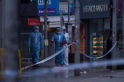 © Licensed to London News Pictures. 14/12/2020. HARROW, UK. Forensics officers in Station Road sheltering from the rain. A man, believed to be in his 20s, has died and two others, believed to be in their late-teens, have been injured in a stabbing Station Road in Harrow, north west London. The Met Police said emergency services were called to the area at 19:15 GMT on Sunday 13 December to reports of a stabbing.  A crime scene remains in place.  Photo credit: Stephen Chung/LNP
