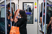 Passengers some of them wearing face protective masks to curb the spread of the pandemic outbreak, hold on to the rail as they travel on Jubilee Line southbound to Stratford in London on Saturday, Aug 7, 2021. Department of Health reported that a further 28,612 infections, a 9.6 per cent since last Saturday's figure of 26,144 have increased. The number of people dying from the virus has increased to 103. (VX Photo/ Vudi Xhymshiti)