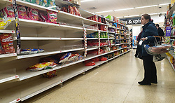 © Licensed to London News Pictures. 27/10/2021. London, UK. A shopper looks at nearly empty shelves of Walkers crisp in Sainsbury's, north London, as food shortages continue, following Brexit. According to the British Retail Consortium, three in five retailers expect prices to increase in the run up to Christmas, and the ongoing labour shortages are making the situation worse. Photo credit: Dinendra Haria/LNP