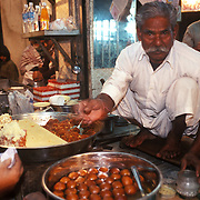 A sweet vendor in old delhi selling Gajar ka Halwa and Gulab Jamun. The art of making halwa with nuts was introduced in India during the Moghul period by the traders from the Middle East and Asia. It is the Indian cooks, however, who are credited with making halwa by using vegetables such as carrots, pumpkin, zucchini, snake squash, winter melon, potatoes, and yams. This glazed carrot halwa, a specialty of the Sikhs of Punjab, is the most popular halwa in India and is enjoyed as a dessert as well as a sweet.
