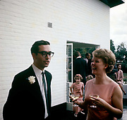 Young European couple at friends' wedding reception in Blantyre, Malawi in the mid-1960s. The woman holds two glasses of perhaps champagne and laughs out loud at a joke or quip that her male friend has told. There are bridesmaids behind them on the patio terrace where other guests enjoy the happy at the happy reception for ex-pat Europeans living in this central African state.